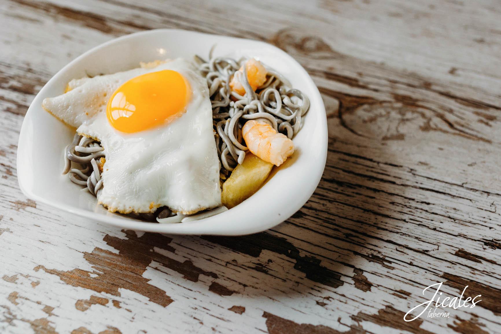huevos rotos con gulas y langostinos